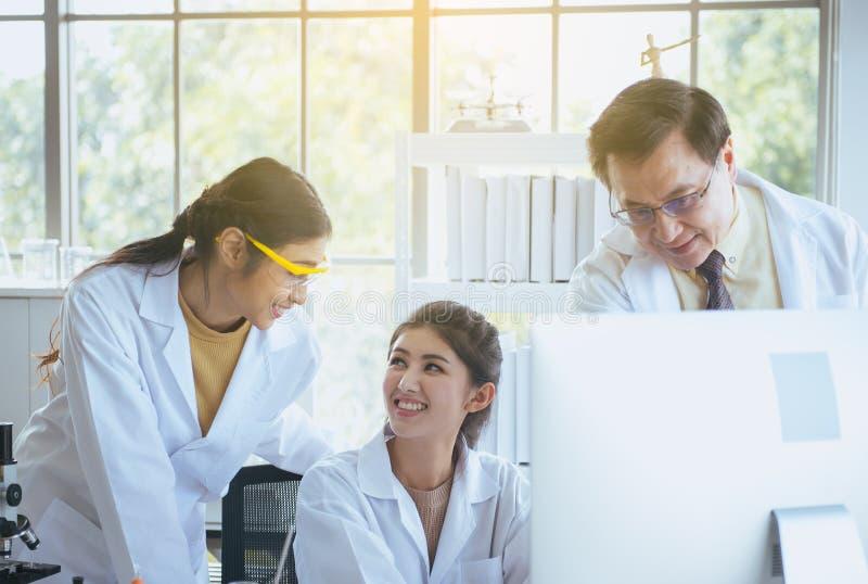 Grupp av den asiatiska medicinaren som tillsammans arbetar och analyserar information om dataforskning i det laboratary royaltyfri bild
