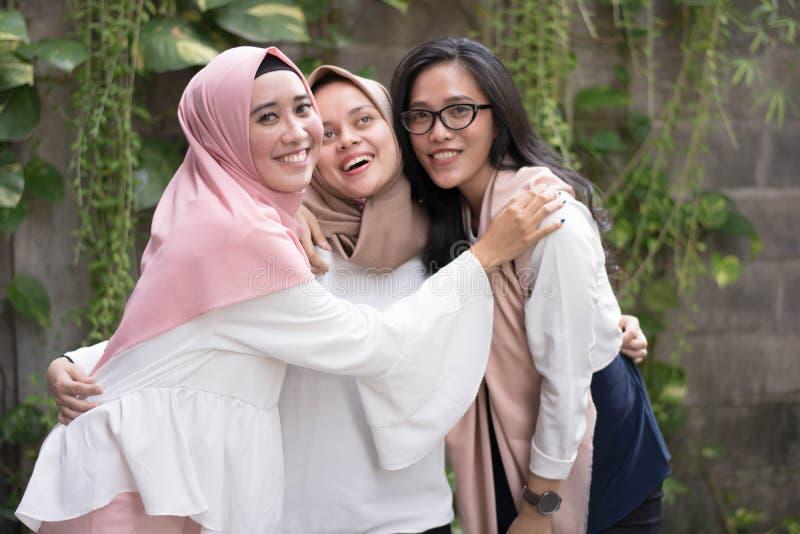 Grupp av den bästa djävulmuslimflickan som ler på kameran, medan krama fotografering för bildbyråer