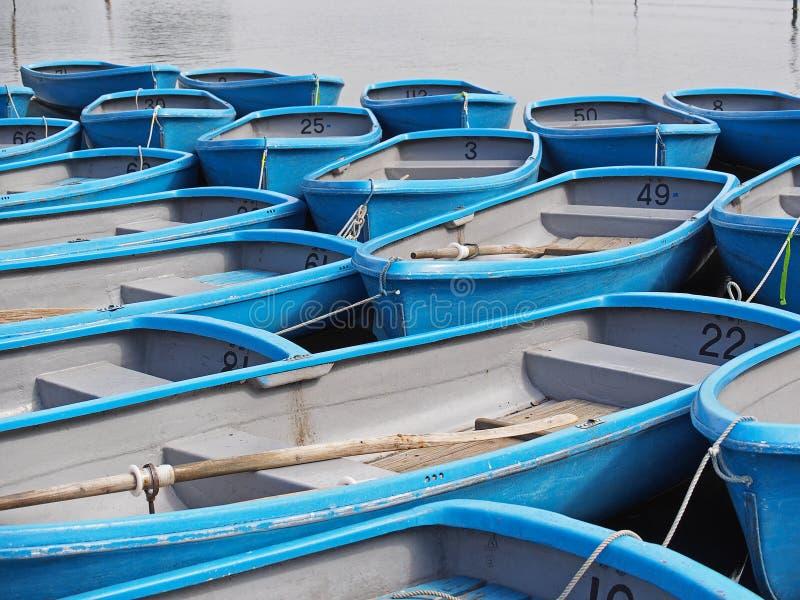 Grupp av den blåa roddbåten på floden fotografering för bildbyråer