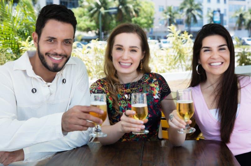 Grupp av den caucasian och latinska mannen och kvinnan som dricker öl i en stång royaltyfri fotografi