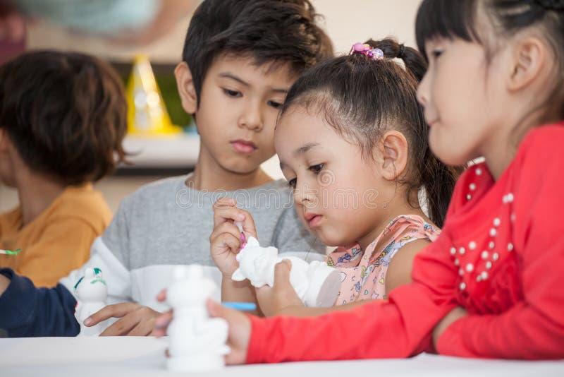 Grupp av den gulliga liten flickastudenten som målar en keramisk krukmakerimodell i klassrumskola Ungekonstn?r barn som sitter på royaltyfria foton