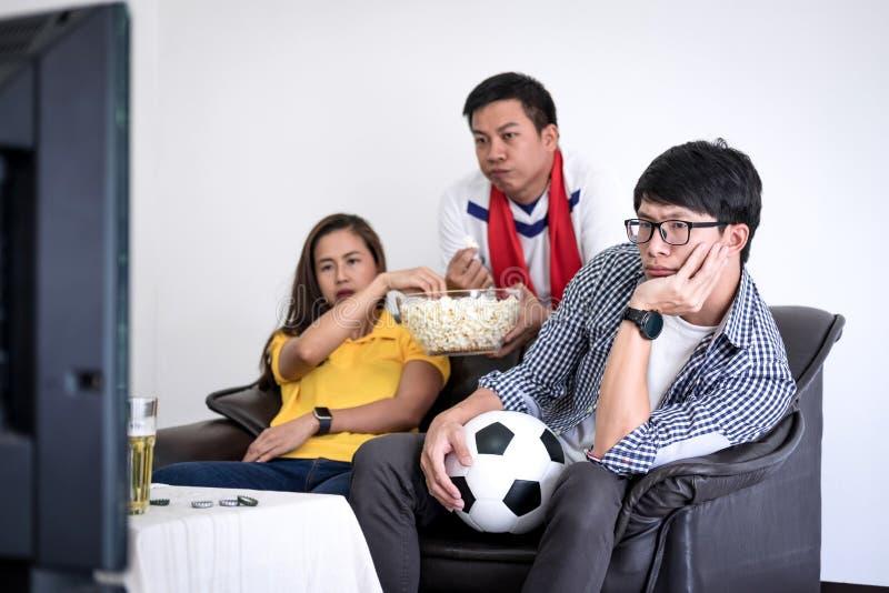 Grupp av den hållande ögonen på fotbollsmatchen för vänfanclub på tv och cheerin arkivfoton