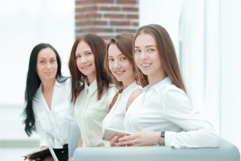 Grupp av den lyckade aff?rskvinnan som i regeringsst?llning sitter korridoren Foto med kopieringsutrymme royaltyfri foto