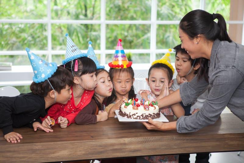 grupp av den lyckliga barnflickan med hatten som blåser stearinljus på födelsedagkakan som firar tillsammans i parti ungar samlad royaltyfri fotografi