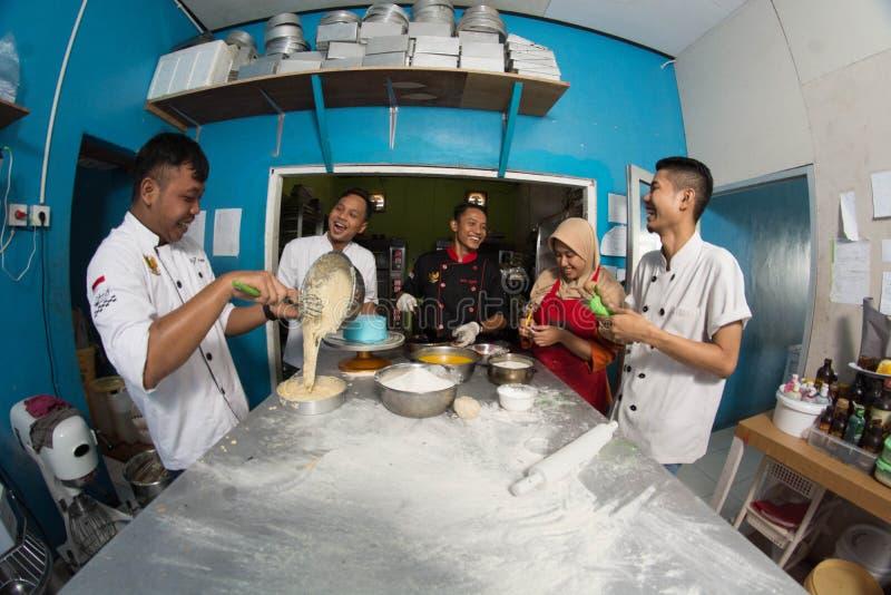Grupp av den lyckliga unga asiatiska bakelsebagerikocken som förbereder deg med mjöl som arbetar inom kök royaltyfria bilder