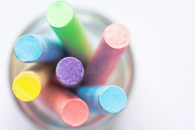Grupp av den mångfärgade koppen för Chalksfärgpennor med blyerts Vitbakgrund för bästa sikt Kreativitet för utbildningskonsthantv royaltyfri foto