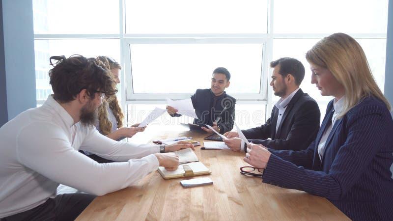 Grupp av den unga affärsmannen på förhandlingsbordet i kontoret Kollegablick till och med dokument Ett affärsmöte royaltyfri bild