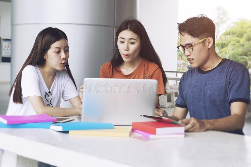 Grupp av den unga asiatet som studerar i universitetet som sitter under att studera för universitet för högskola för föreläsnings royaltyfria bilder