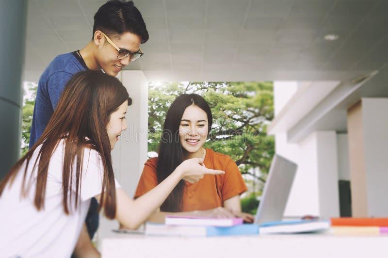 Grupp av den unga asiatet som studerar i universitetet som sitter under universitet för högskola för föreläsningsutbildningsstude arkivbilder