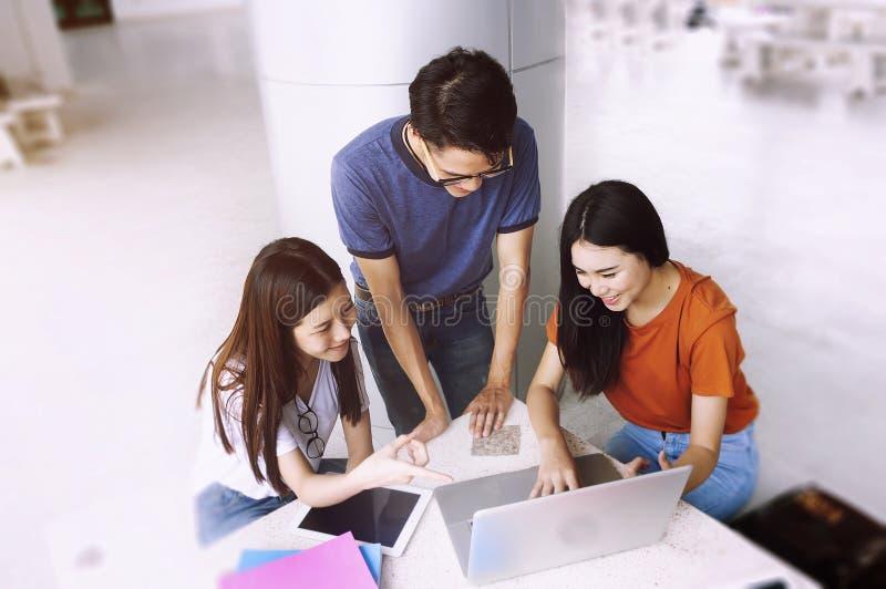 Grupp av den unga asiatet som studerar i universitetet som sitter under universitet för högskola för föreläsningsutbildningsstude royaltyfria bilder
