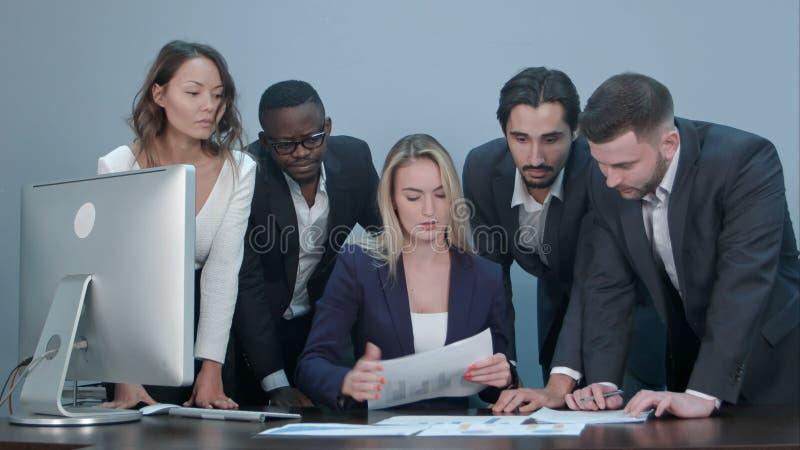 Grupp av den upptagna diskuterande ekonomiska frågan för affärsfolk under möte som står runt om det kvinnliga framstickandeskrivb arkivbild