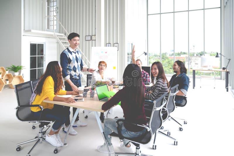 Grupp av det blandras- unga id?rika laget som talar, skrattar och id?kl?ckning i m?te p? det moderna kontorsbegreppet Mananseende royaltyfri foto
