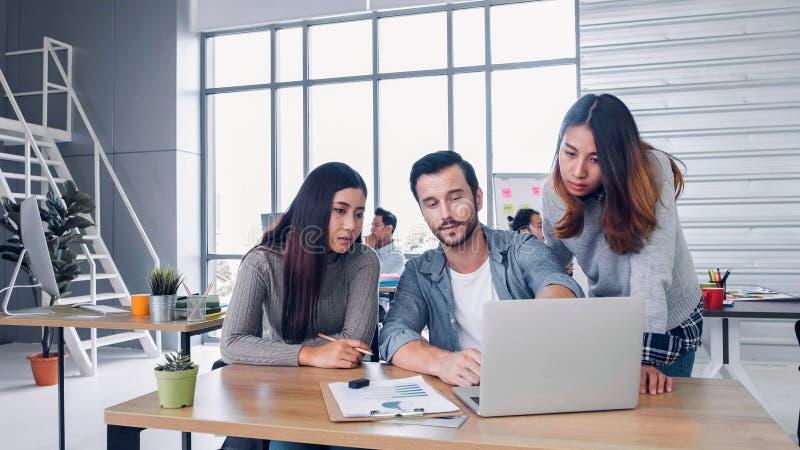 Grupp av det idérika märkes- tillfälliga mötet med bärbara datorn på det moderna kontoret i morgon på skrivbordet r arkivfoton