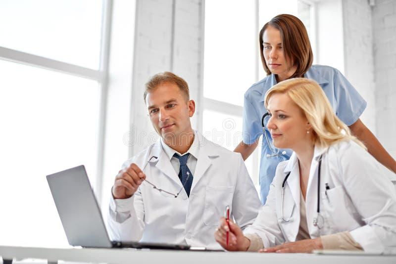 Grupp av doktorer med bärbar datordatoren på sjukhuset arkivbilder