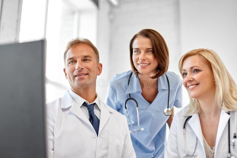 Grupp av doktorer med datoren på sjukhuset royaltyfri fotografi