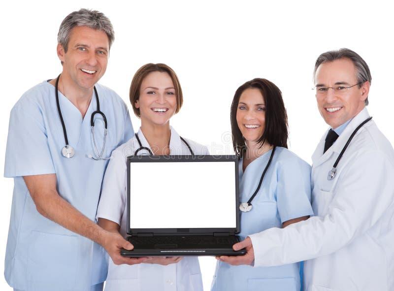 Grupp av doktorer med en bärbar dator arkivbilder