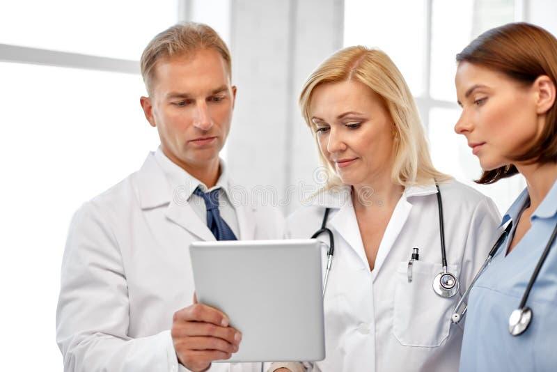 Grupp av doktorer med minnestavladatoren på sjukhuset royaltyfri bild