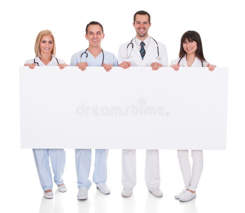 Grupp av doktorer med plakatet royaltyfri bild