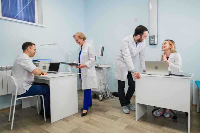 Grupp av doktorer som är involverade i allvarlig diskussion med sjukdomshistorier royaltyfria foton