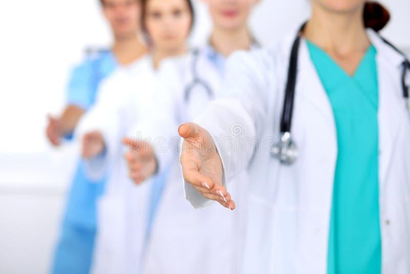 Grupp av doktorer som erbjuder portionhanden i sjukhuscloseup Vänlig och gladlynt gest Medicinsk bot och prov fotografering för bildbyråer