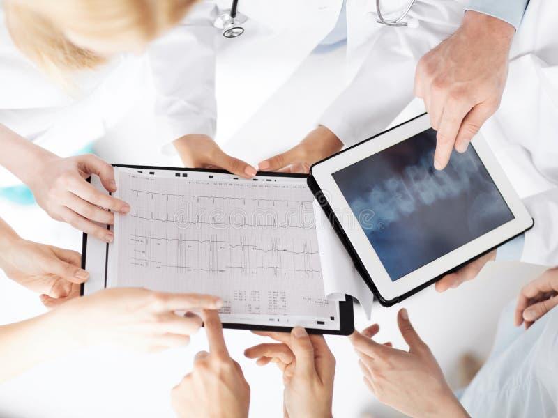 Grupp av doktorer som ser röntgenstrålen på minnestavlaPC royaltyfria foton