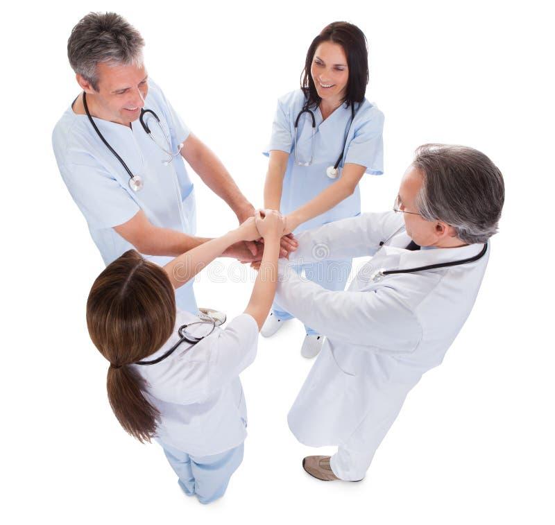 Grupp av doktorer som tillsammans staplar händer arkivfoto