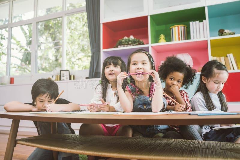 Grupp av dra papper för små förskole- ungar med färgblyertspennor stående av begreppet för barnvänutbildning arkivfoton