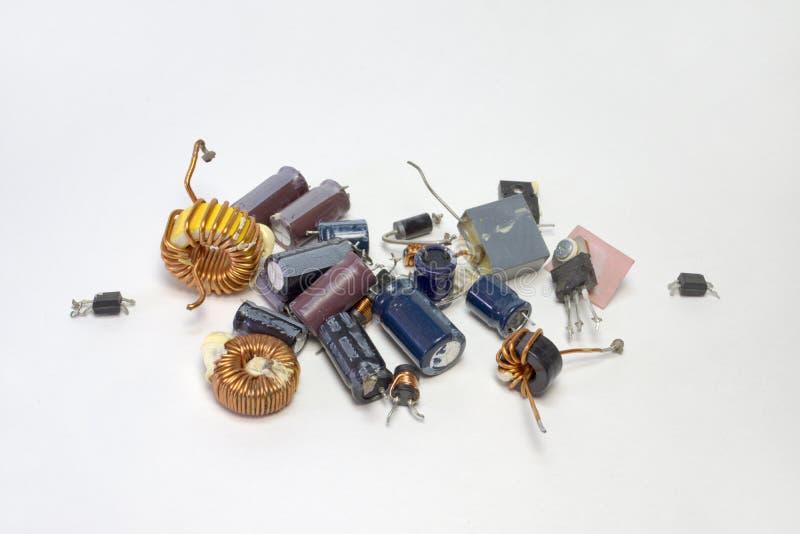 Grupp av elektroniska delar: kondensatorer transistorer, induktionsapparater royaltyfri bild