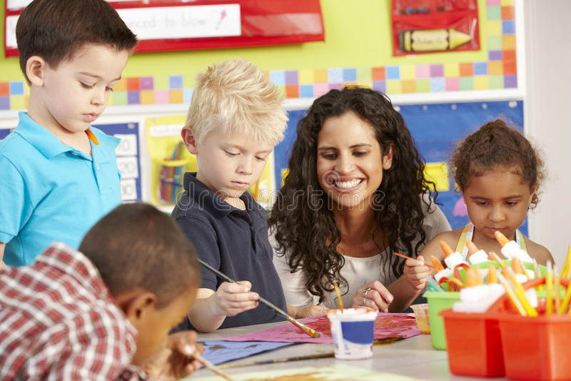 Grupp av elementära ålderskolbarn i Art Class With Teacher royaltyfria bilder
