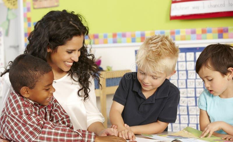 Grupp av elementära ålderskolbarn i grupp med läraren arkivbild