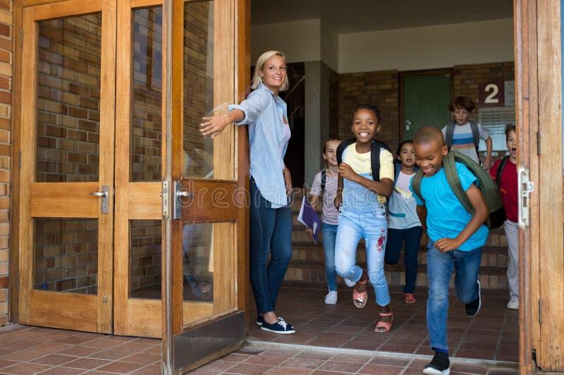 Grupp av elementära barn som kör den utvändiga skolan arkivfoton