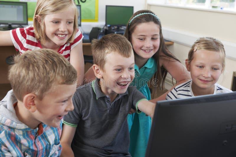 Grupp av elementära elever i datorgrupp arkivbilder
