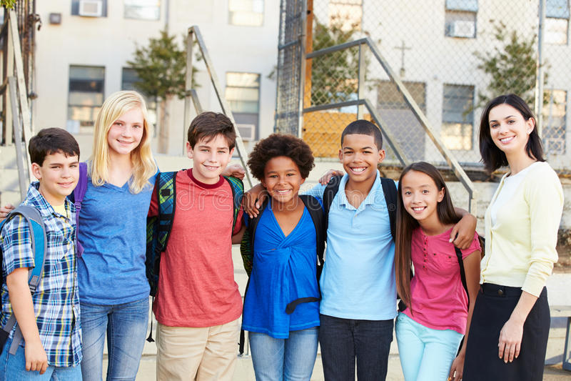 Grupp av elementära elever utanför klassrum med läraren arkivfoton