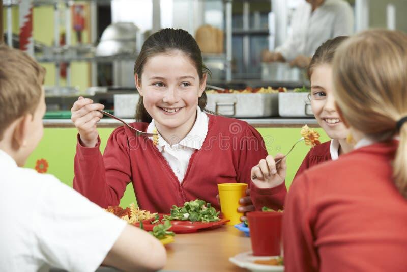 Grupp av elever som sitter på tabellen i skolakafeteria som äter Lunc arkivfoto