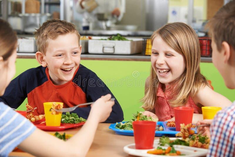 Grupp av elever som sitter på tabellen i skolakafeteria som äter mål royaltyfri fotografi