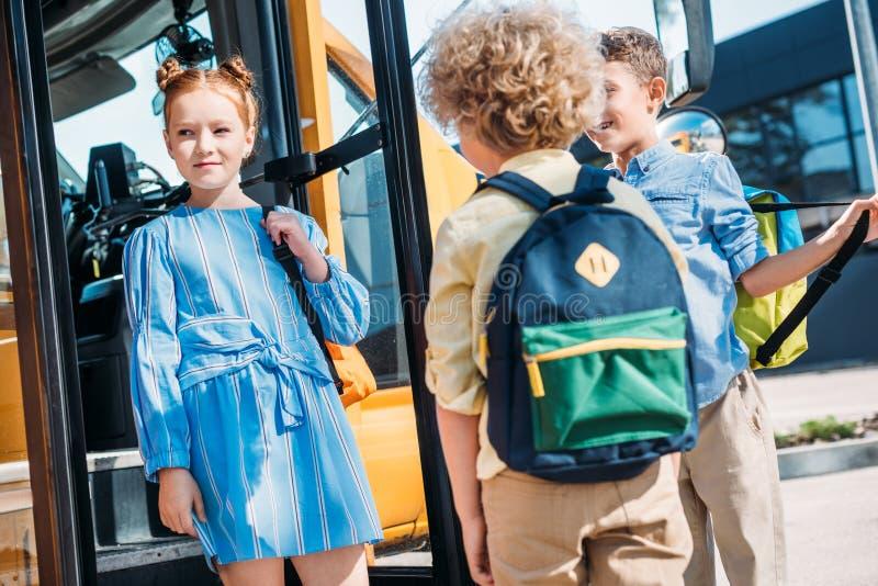 grupp av elever som står nära skolbussen royaltyfri bild