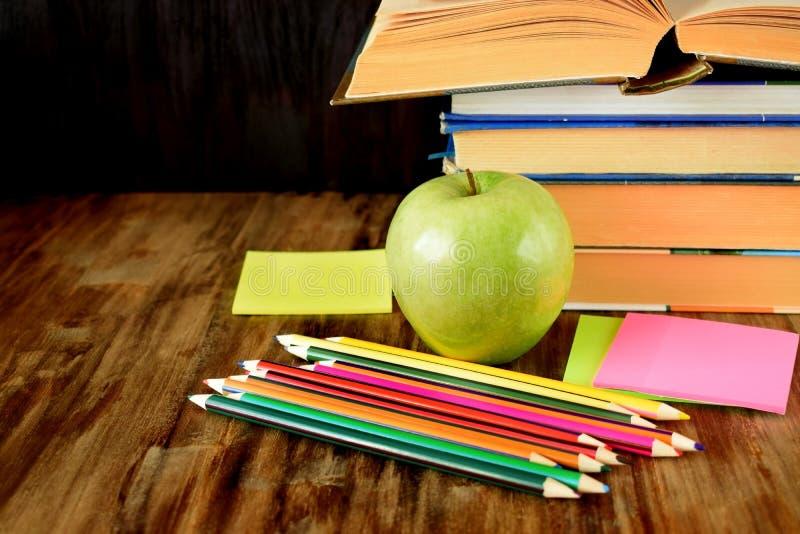 Grupp av färgade blyertspennor, det gröna äpplet, klistermärkear och en hög av böcker royaltyfri foto