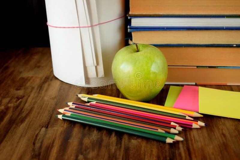 Grupp av färgade blyertspennor, det gröna äpplet, klistermärkear och en hög av böcker arkivfoton
