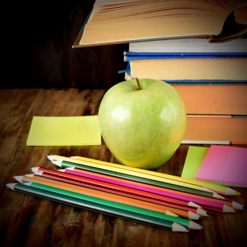 Grupp av färgade blyertspennor, det gröna äpplet, klistermärkear och en hög av böcker royaltyfri bild