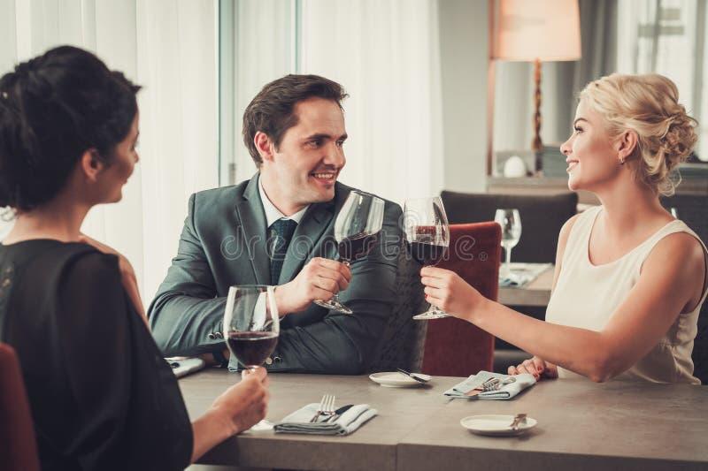 Grupp av förmöget folk som klirrar exponeringsglas av rött vin i restaurang arkivfoton
