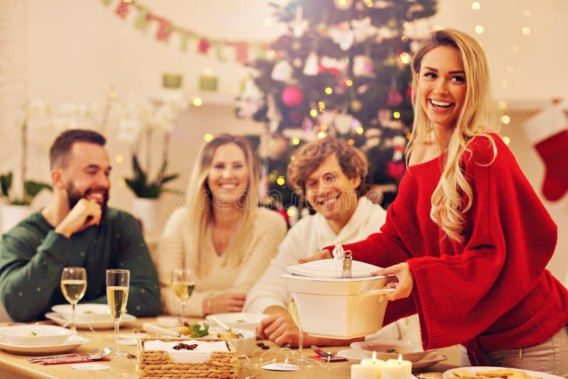 Grupp av familj och vänner som firar julmatställen arkivbilder