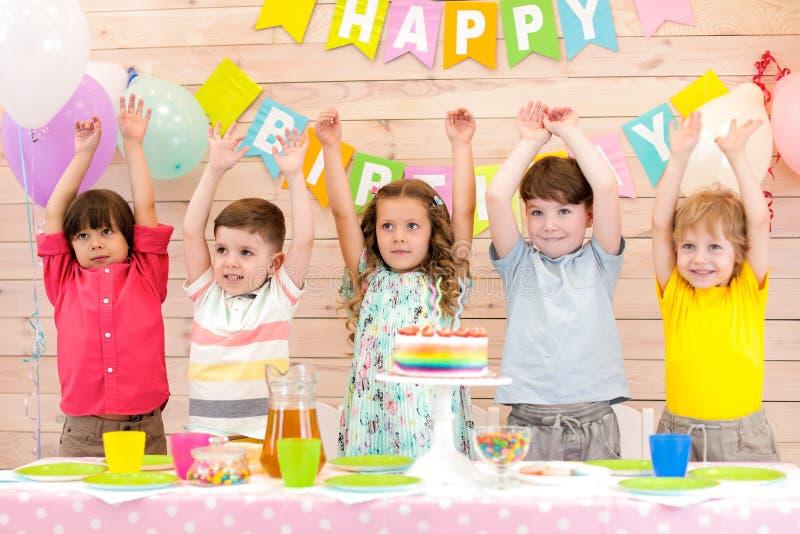 Grupp av fem barn som ler att stå i rad bredvid födelsedagtabellen med kakan på den som rymmer upp händer royaltyfri fotografi