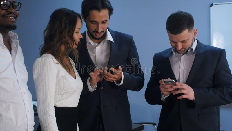 Grupp av fem blandras- affärspersoner som står och använder smartphones fotografering för bildbyråer