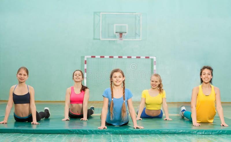 Grupp av fem tonårs- flickor som utarbetar i idrottshall arkivfoton