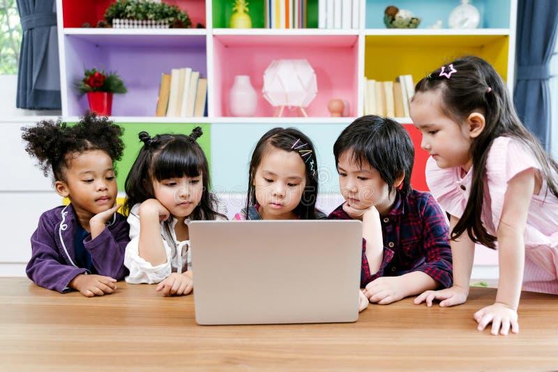 Grupp av filmen för mångfald för små barn den hållande ögonen på tillsammans på bärbara datorn Ungar som hemma spelar med b?rbar  fotografering för bildbyråer