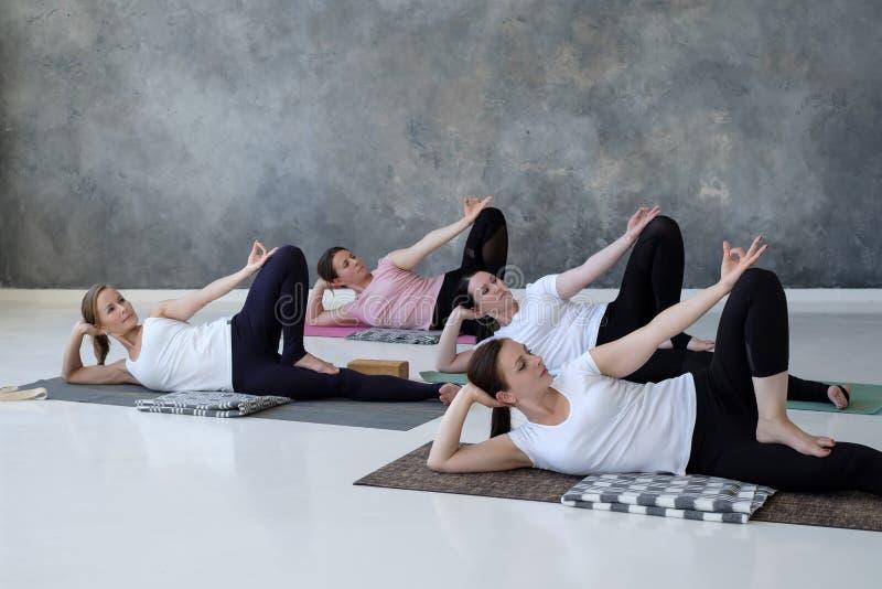 Grupp av flera europeiska kvinnor som gör yogaställingsanantasana arkivfoton