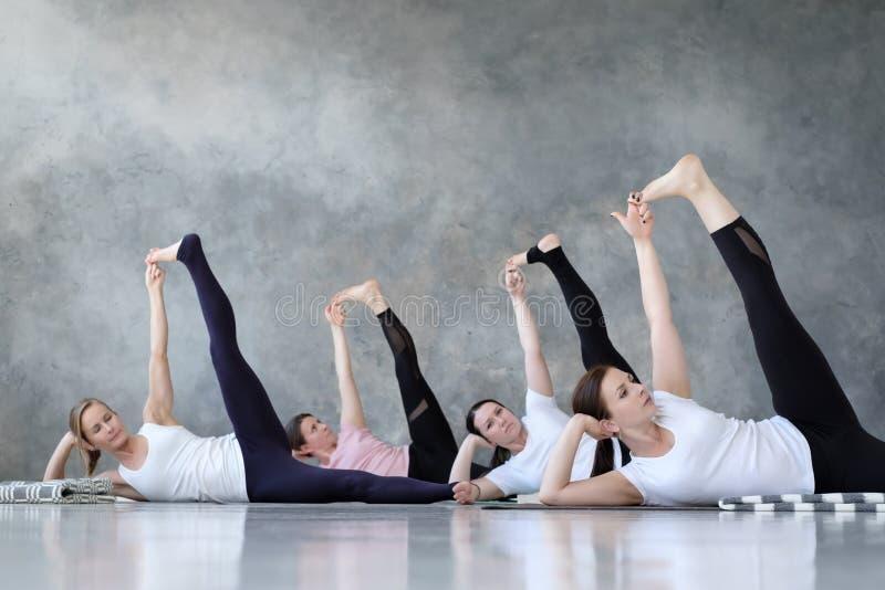 Grupp av flera europeiska kvinnor som gör yogaställingsanantasana arkivbilder