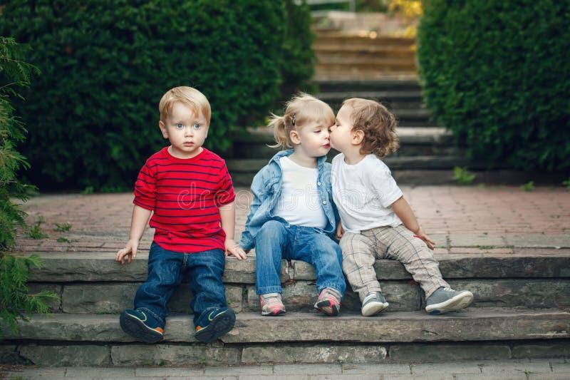 Grupp av flickan för tre den gulliga roliga förtjusande vita Caucasian barnlitet barnpojkar som sitter kyssa sig tillsammans royaltyfri bild
