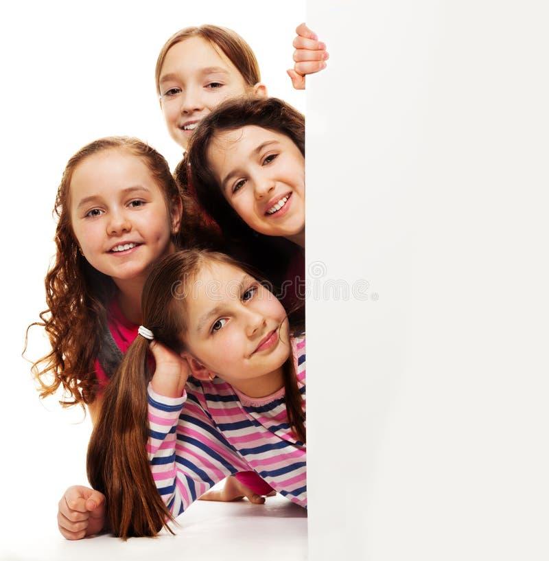 Grupp av flickor bak advertizingbräde royaltyfri fotografi