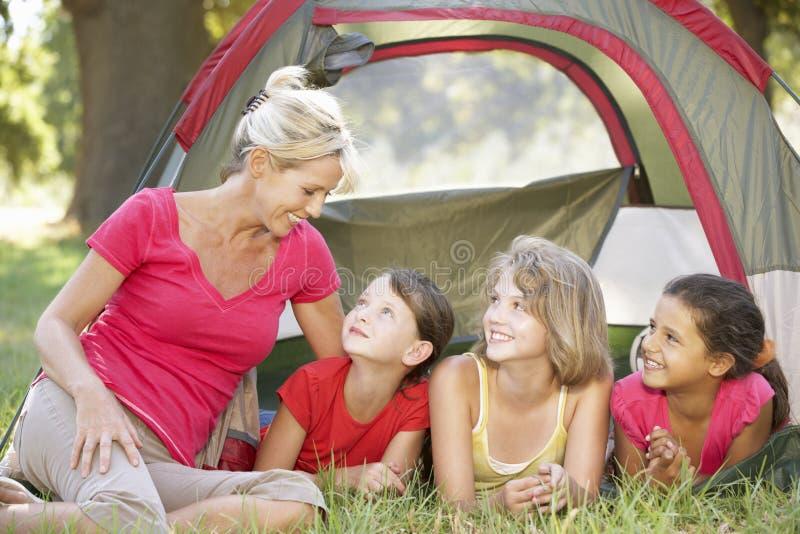 Grupp av flickor med modern som har gyckel i tält i bygd arkivbild
